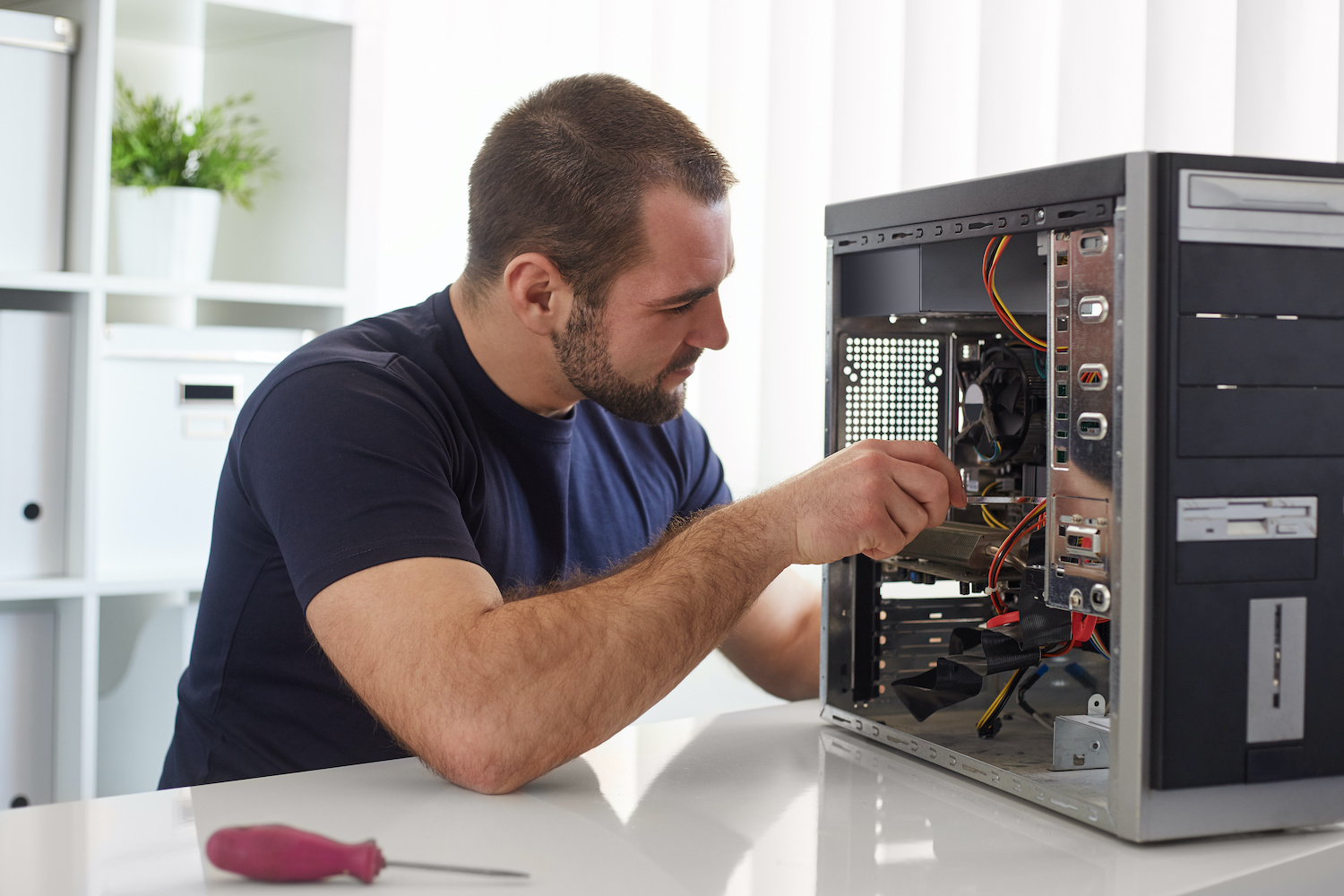 A computer repair technician fixing a computer. Repair technicians help with common computer problems and advanced repairs.
