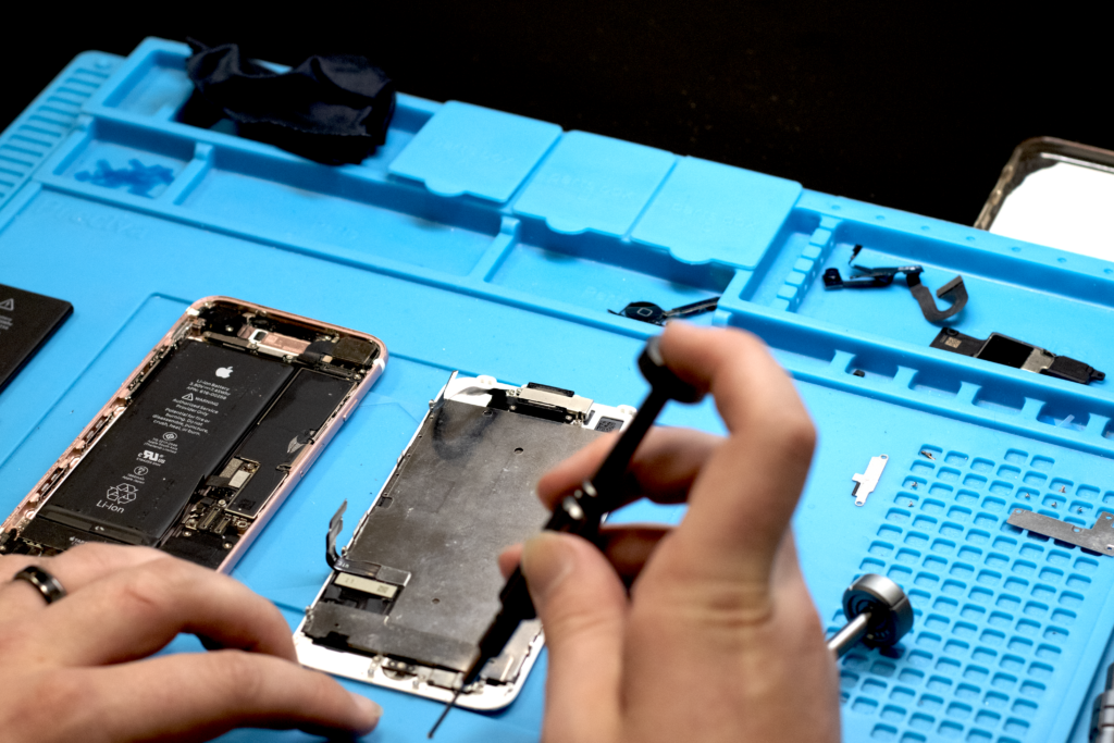 A ScreenWorks repair technician working on a broken phone. Common issues include phone battery draining and cracked screen.