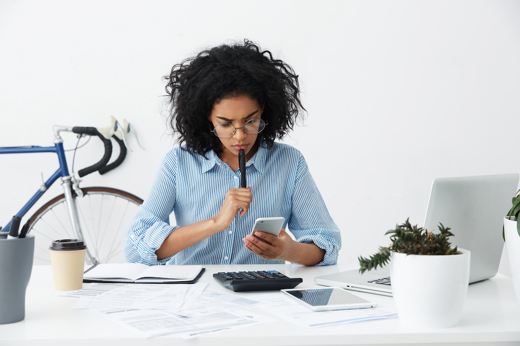 Frustrated female entrepreneur in formal shirt and eyewear having a phone problem while working on a financial report in office.