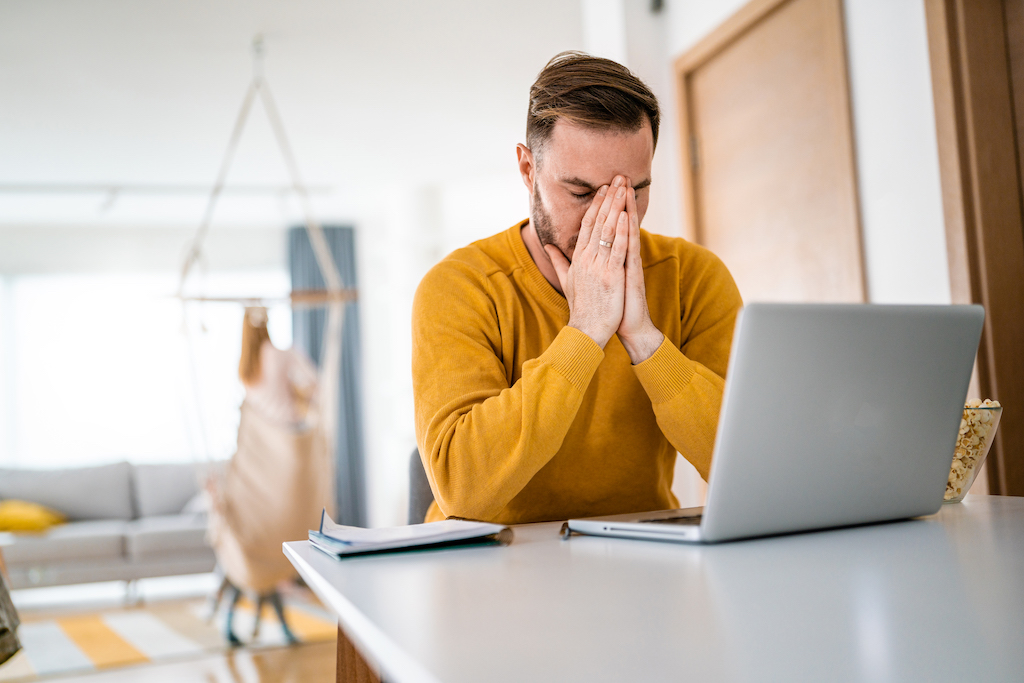 Frustrated young business man working on laptop at home