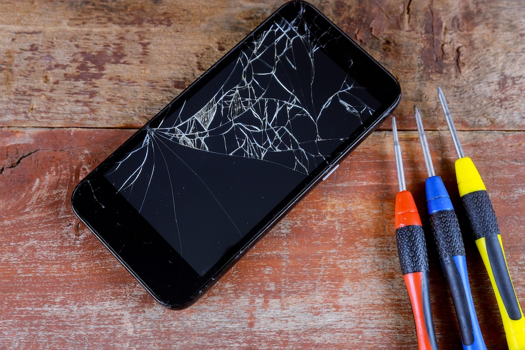 Screwdriver and smartphone with broken screen on a wooden table.