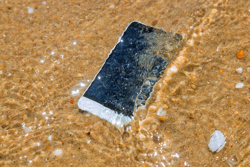 Smart phone with weather on a sandy beach of sea background