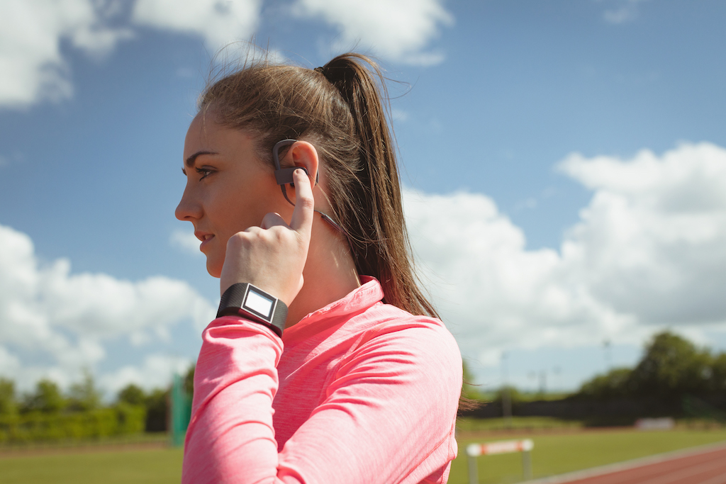 Woman hearing Bluetooth headphones and sports watch that's synced with her phone via Bluetooth.