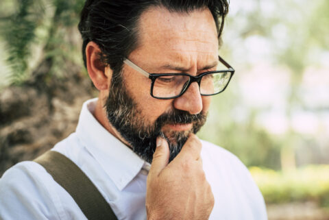 Worried man touching beard trying to figure out how to fix his cell phone.