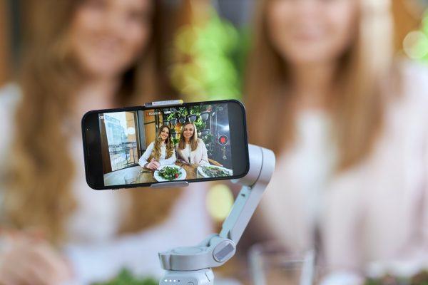 Beautiful young blogger women posing on phone camera