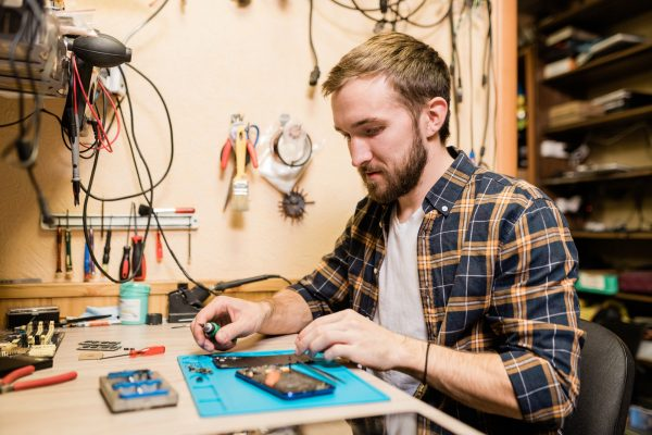 Professional repairman with screwdriver repairing broken smartphone in workshop
