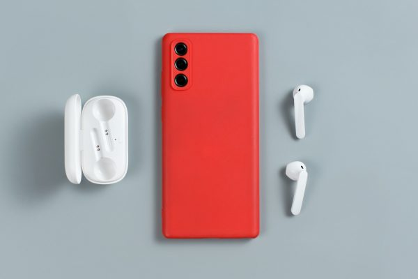 Smartphone with red cover and white wireless earphones