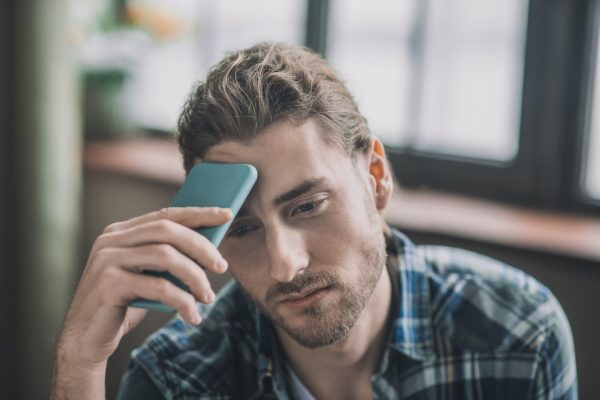 Tired and frustrated men holding his mobile phone